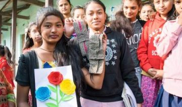 Girls display the reusable sanitary towels we helped them make.